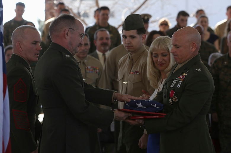 MARINE CORPS BASE CAMP PENDLETON, Calif. – Colonel Willard 'Willy' Buhl is awarded a Distinguished Service Medal and given an honorable discharge certificate along with a commemorative flag for his retirement ceremony on Feb. 12, at Camp Pendleton, Calif. The ceremony was to commemorate Buhl's 34 years of dedicated service to the United States Marine Corps. Buhl was formerly the director of Expeditionary Operations Training Group, I Marine Expeditionary Force and is from Los Gatos, Calif. (U.S. Marine Corps photo by Cpl. Angel Serna/Released)