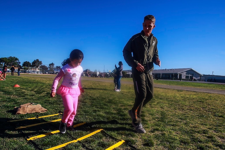 MARINE CORPS BASE CAMP PENDLETON, Calif. – Lance Cpl. George Cofield, right, guides Samantha Torres through an obstacle course at North Terrace Elementary, March 25, 2016. Approximately 30 Marine volunteers with the Single Marine Program facilitated a series of exercises and competitions including an obstacle course relay race and tug-of-war as part of a Physical Education Fitness Challenge. The challenge encourages children to stay active and helps Marines engage with their local community. Cofield, a native of Windsor, Va., is an aviation mechanic with Marine Aviation Logistics Squadron 39, Marine Aircraft Group 39, 3rd Marine Aircraft Wing, I Marine Expeditionary Force. Torres is a kindergarten student at North Terrace Elementary. (U.S. Marine Corps photo by Lance Cpl. Caitlin Bevel/RELEASED)