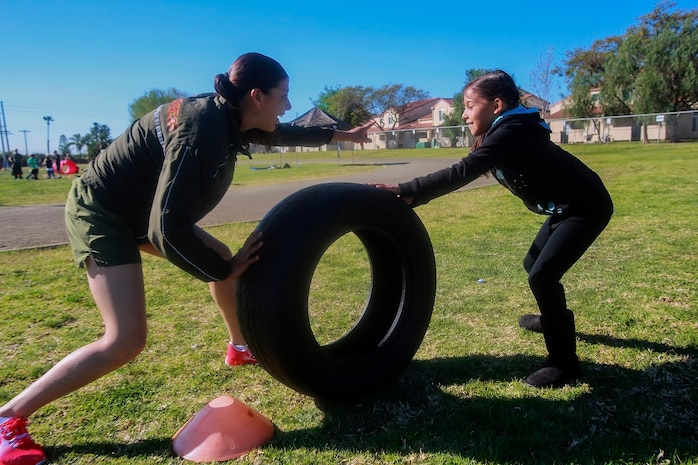 MARINE CORPS BASE CAMP PENDLETON, Calif. – Cpl. Richelle Delapaz, left, guides Kayla Morley through an obstacle course at North Terrace Elementary, March 25, 2016. Approximately 30 Marine volunteers with the Single Marine Program facilitated a series of exercises and competitions including an obstacle course relay race and tug-of-war as part of a Physical Education Fitness Challenge. The challenge encourages children to stay active and helps Marines engage with their local community. Delapaz, a native of Corpus Christi, Texas, is a field radio operator with 9th Communication Battalion, I Marine Expeditionary Force Headquarters Group. Morley is a second grade student at North Terrace Elementary. (U.S. Marine Corps photo by Lance Cpl. Caitlin Bevel/RELEASED)
