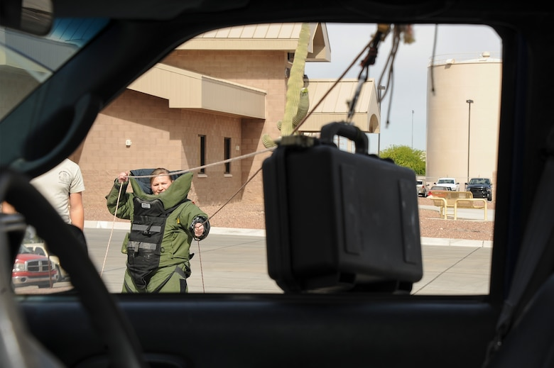U.S. Air Force Master Sgt. Hass, 355th Civil Engineer Squadron first sergeant, uses a hook and line procedure to remotely remove a suspicious package from a vehicle during the Comprehensive Airman Fitness Month Fire Department Fitness Challenge at Davis-Monthan Air Force Base, Ariz., March 31, 2016.  The event was hosted by the 355th Civil Engineer Squadron's explosive ordnance disposal and fire emergency service flights in coordination with the Community Support Center with the objectives of embracing team building, showing the links between different CAF pillars, and encouraging Airmen to challenge themselves. (U.S. Air Force photo by Airman 1st Class Mya M. Crosby/Released) (U.S. Air Force photo by Airman 1st Class Mya M. Crosby/Released)