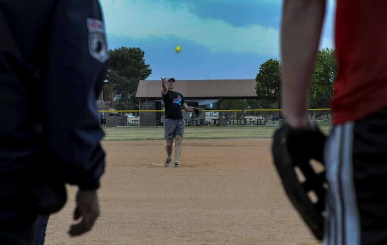A member of the 57th Operations Support Squadron team from Creech Air Force Base pitches against the 30th Reconnaissance Squadron during the first intramural game of the day at Nellis Air Force Base, Nev., March 29, 2016.  With the season beginning in the middle of March, the league is planned to be finished during May before the summer temperatures get to hot to play. (U.S. Air Force photo by Airman 1st Class Kevin Tanenbaum)