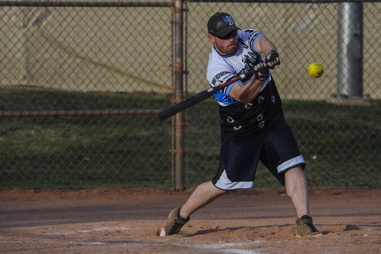 A team member from the 57th Maintenance Squadron Munitions Flight intramural softball team swings at a pitch during a practice before a game at Nellis Air Force Base, Nev., March 28, 2016. The Warrior Fitness Center hopes that Airmen can have fun playing softball; the intramural league is also used as a way to build on the four pillars of comprehensive fitness. (U.S. Air Force photo by Airman 1st Class Kevin Tanenbaum)