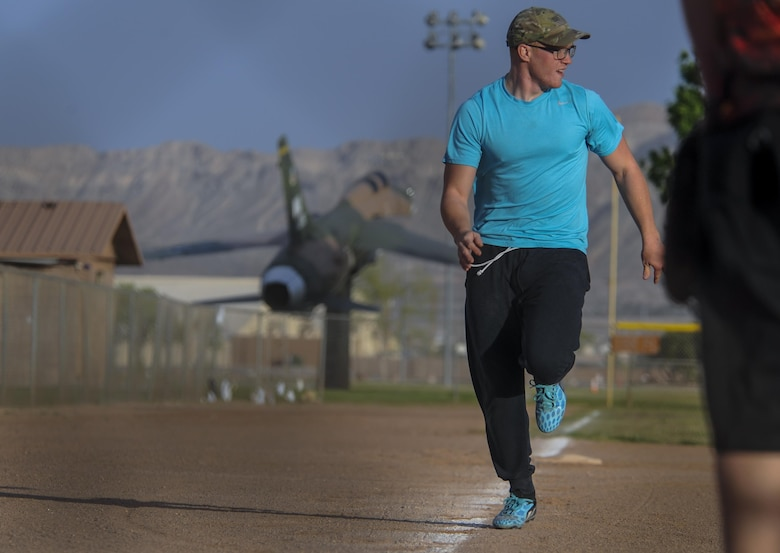 A 57th Maintenance Squadron Munitions Flight intramural softball team member sprints towards home plate during a practice before a game at Nellis Air Force Base, Nev., March 28, 2016. The Airmen hope to take away a healthier atmosphere, both physically and mentally. The dynamic of teams allows for a fun, competitive environment that gets teams interacting within and outside their units. (U.S. Air Force photo by Airman 1st Class Kevin Tanenbaum)