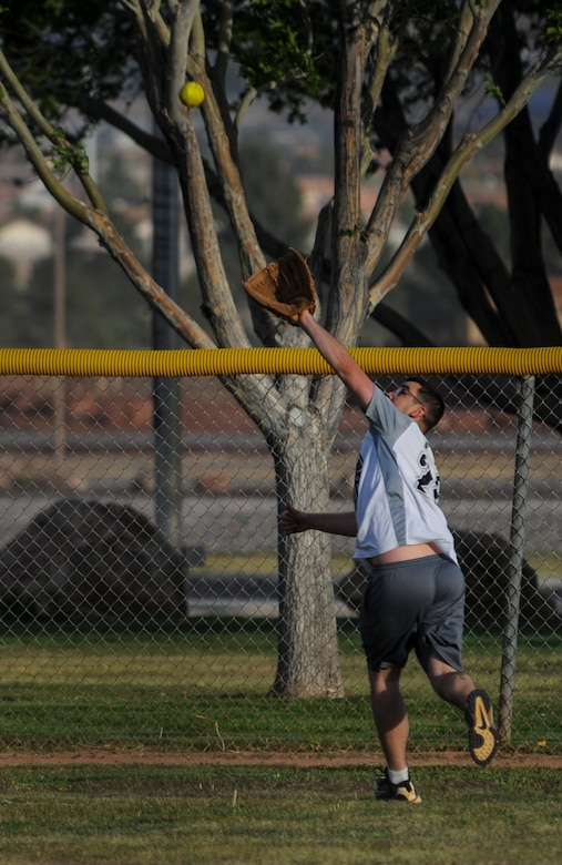 A player from the 57th Maintenance Squadron Munitions Flight intramural softball team attempts to catch a fly ball on the run during a practice game at Nellis Air Force Base, Nev., March 28, 2016. Softball games, which are held Monday through Thursday from 5:30 to 7:30 p.m., are meant to build goodwill between the units. (U.S. Air Force photo by Airman 1st Class Kevin Tanenbaum)