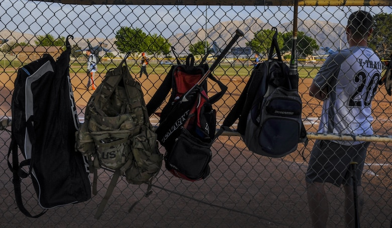 Duffle bags hang on the fence as a member of the 57th Operations Support Squadron intramural softball team waits for his turn to bat during a practice game at Nellis Air Force Base, Nev., March 29, 2016. Softball games, which are held Monday through Thursday from 5:30 to 7:30 p.m., are meant to build goodwill between the units. (U.S. Air Force photo by Airman 1st Class Kevin Tanenbaum)