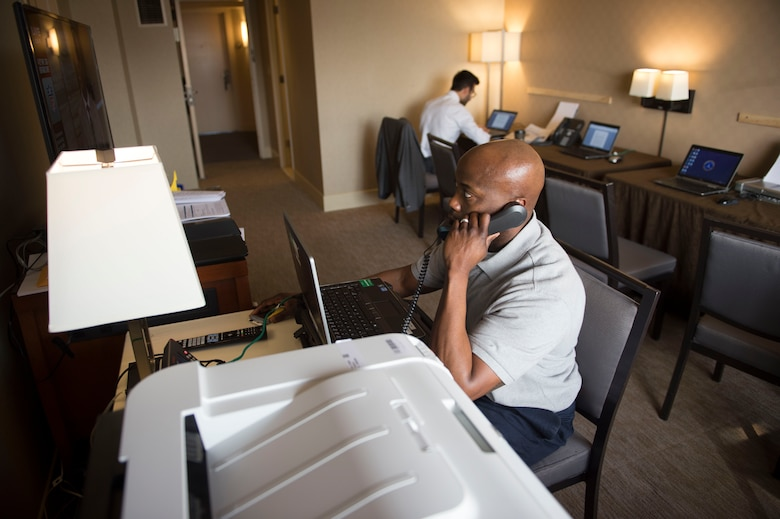 Tech. Sgt. Demond Bush makes a phone call in a communications room set up in the hotel where Defense Secretary Ash Carter and his staff stayed during a recent trip to the West Coast. The Air Force tech support staff provides 24/7 access to secure networks, Internet, printers and phones. (U.S. Air Force photo)
