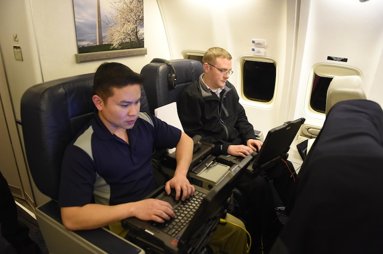 Tech. Sgts. Jacques Mcanlay, left, and Jared Engler provide tech and communications support to Defense Secretary Ash Carter and his staff aboard a C-32 military aircraft during a recent trip to the West Coast. (U.S. Air Force photo)