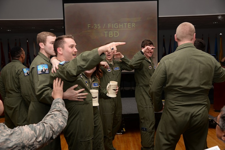 Second Lt. Austin Hornsby, Specialized Undergraduate Pilot Training Class 16-07, celebrates with his flightmates after receiving his assignment to fly the F-35 Lightning II at 16-07 assignment night on Columbus Air Force Base, Mississippi, March 25. Hornsby will be the first SUPT student ever to accept the challenge of piloting the F-35. (U.S. Air Force photo illustration/Senior Airman Stephanie Englar)