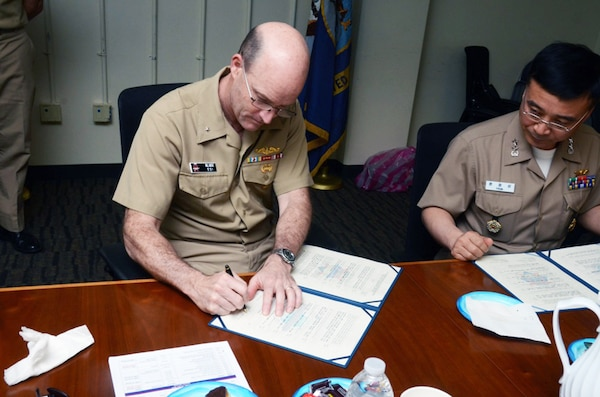 SANTA RITA, Guam (March 31, 2016) - Rear Adm. William Merz, commander, Submarine Group 7, left, and Rear Adm. Youn Jeong Sang, commander, Submarine Force, Republic of Korea Navy (ROKN), sign a formal agreement at the conclusion of the 43rd Submarine Warfare Committee Meeting (SWCM) reaffirming the longstanding relationship between the two countries and pledging continued support between the two submarine forces. SWCM is a bilateral discussion between the U.S. and ROKN submarine forces designed to foster the partnership and focuses on submarine tactics, force integration and future submarine development.