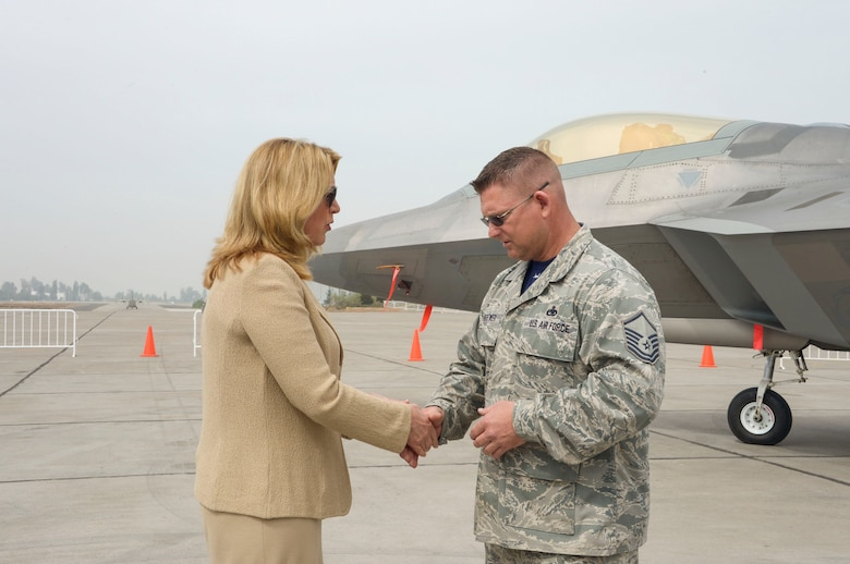 Deborah Lee James, Secretary of the Air Force, coins Master Sgt. Ambrose Brewer, F-22 Raptor Demonstration Team lead planner, during the 2016 FIDAE Air and Space Trade Show in Santiago, Chile, March 29, 2016. During the FIDAE Air and Space Trade Show, U.S. Airmen participated in in several subject matter expert exchanges with their Chilean counterparts and also hosted static displays and aerial demonstrations to support the air show.  (U.S. Air Force photo by Tech. Sgt. Heather Redman/Released)