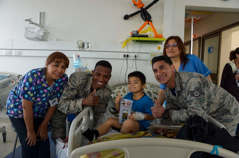 Senior Airman Tyrell Noriega and Staff Sgt. Juan Gomez-Navarro, F-22 Demonstration Team members, pose with a child at San Juan de Dios hospital in Santiago, Chile, March 31, 2016.  The Airmen are in Chile to participate in the 2016 FIDAE Air and Space Trade Show and spent some of their down-time visiting children in multiple hospitals.  (U.S. Air Force photo by Tech. Sgt. Heather Redman/Released)