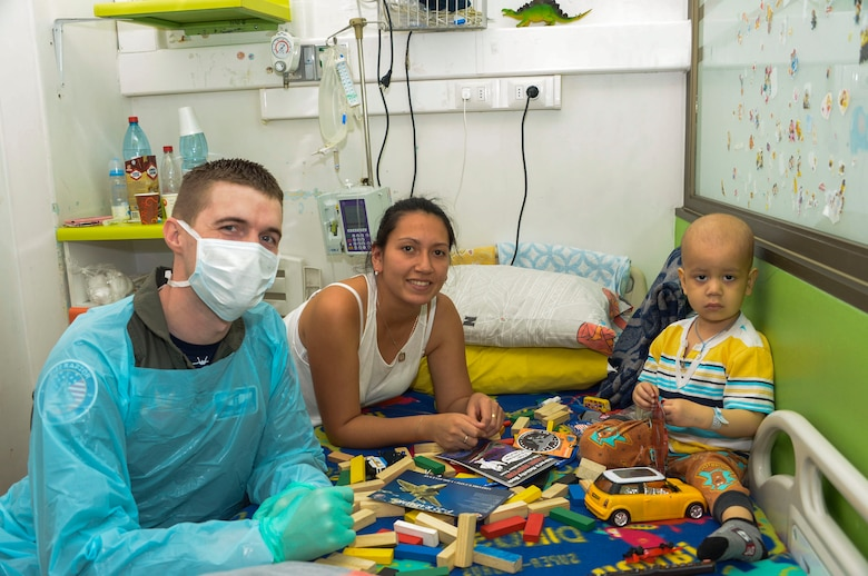 Capt. Stephen Kasteler, flight doctor with the F-22 Demonstration Team, poses with a child at San Juan de Dios hospital in Santiago, Chile, March 31, 2016.  The Airmen are in Chile to participate in the 2016 FIDAE Air and Space Trade Show and spent some of their down-time visiting children in multiple hospitals.  (U.S. Air Force photo by Tech. Sgt. Heather Redman/Released)