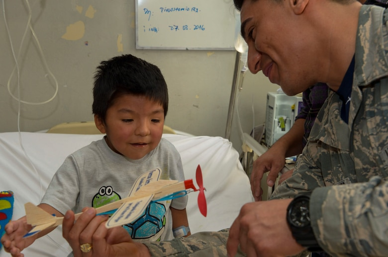 Staff Sgt. Juan Gomez-Navarro, fuel systems specialist with the F-22 Demonstration Team, helps a child build a plane at San Juan de Dios hospital in Santiago, Chile, March 31, 2016.  The Airmen are in Chile to participate in the 2016 FIDAE Air and Space Trade Show and spent some of their down-time visiting children in multiple hospitals.  (U.S. Air Force photo by Tech. Sgt. Heather Redman/Released)
