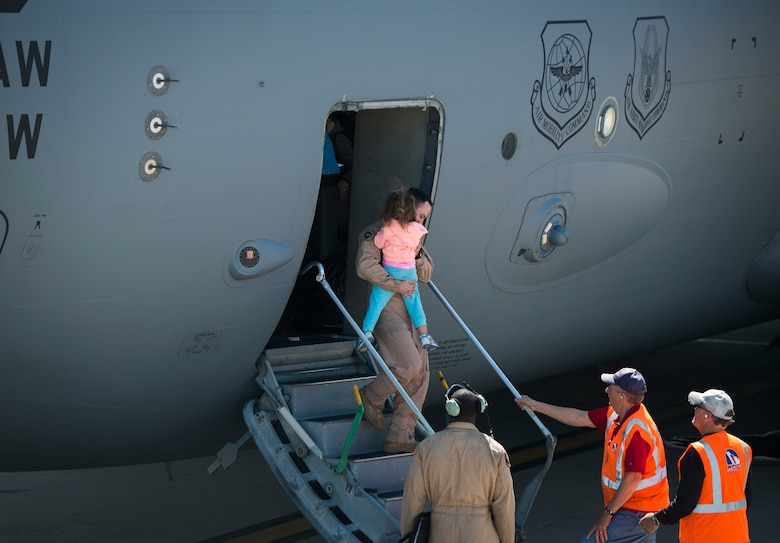 An Air Force crewmember carries a military dependent out of a C-17 Globemaster III at Baltimore Washington International Airport, Md., April 1, 2016. Defense Department dependents in Adana, Izmir and Mugla, Turkey, were given an ordered departure by the State Department and Secretary of Defense. (U.S. Air Force photo/Staff Sgt. Andrew Lee)