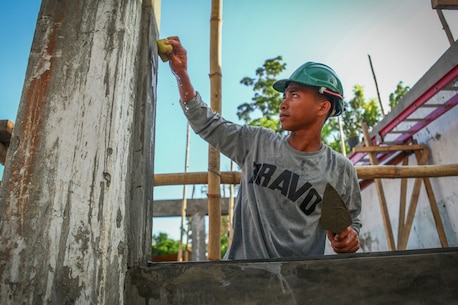"""Philippine army soldier Cpl. Joey Canitan, engineer, assigned to the 552 Engineer Construction Battalion, flattens a layer of cement to help build a classroom for the Jaena Norte Elementary School, in Capiz, Philippines, during Exercise Balikatan, March 29, 2016. The construction project is one of multiple HCAs taking place during this year's exercise, designed to improve the quality of life for the local populace and strengthen the bond between our two nations. Balikatan, which means """"shoulder to shoulder"""" in Filipino, is an annual bilateral training exercise aimed at improving the ability of Philippine and U.S. military forces to work together during planning, contingency and humanitarian assistance and disaster relief operations."""