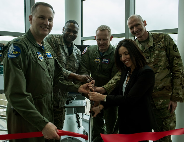 (From left to right) U.S. Air Force Col Timothy Robinette, U.S. Air Forces in Europe and Air Forces Africa command surgeon (left), Col. Alfred Flowers, 52nd Medical Group commander, Col. Joe McFall, 52nd Fighter Wing commander, U.S. Army Col. Kirk Waibel, Army Regional Health Command Europe Telehealth medical director, Alicia English, Army Regional Health Command Europe acting deputy to the command general, cut a ribbon during the 52nd MDG/Landstuhl Regional Medical Center Telehealth ribbon cutting ceremony inside the 52nd MDG clinic April 1, 2016, at Spangdahlem Air Base, Germany. The Telehealth program will allow patients from Spangdahlem Air Base to receive treatment from LRMC doctors without leaving the installation. (U.S. Air Force photo by Senior Airman Rusty Frank/Released)