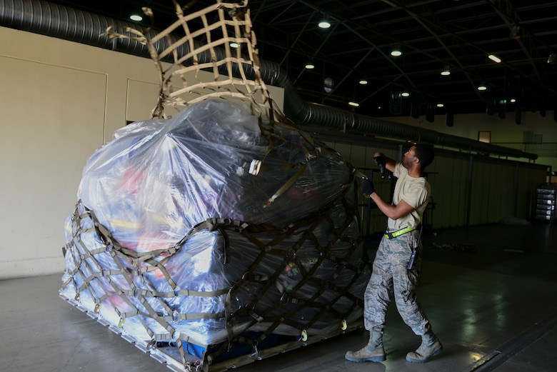 U.S. Air Force Airman Ennis Roberson, 728th Air Mobility Squadron aircraft service apprentice, throws a tie-down net over a pallet of luggage, March 31, 2016, at Incirlik Air Base, Turkey. Pallets were built and staged to load in aircraft for Department of Defense dependents assigned to Incirlik AB. (U.S. Air Force photo by Staff Sgt. Caleb Pierce/Released)