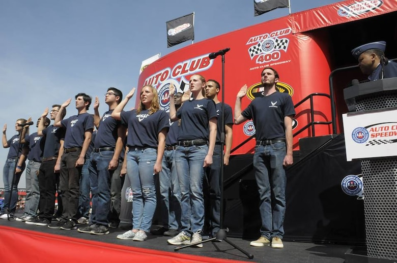 Lt. Gen. Samuel Greaves, SMC commander and Air Force program executive office for space, administers the oath of enlistment for Air Force Delayed Entry recruits during a racing event at the Auto Club Speedway, March 20. (US Air Force photo/Joe Juarez)