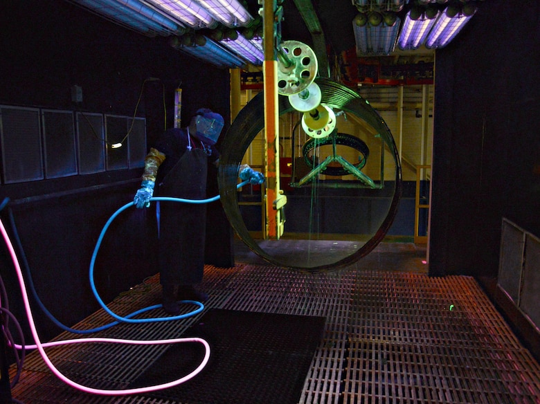Tracy McGehee, a fluorescent penetrant inspector with the 548th Propulsion Maintenance Squadron, rinses a florescent penetrant wash off of a liner duct for a combustion chamber off of an F101 engine in a bay in his shop area. After the part has been thoroughly rinsed and dried, it will be sent to the blacklight room, where inspectors will be able to quickly detect any compromises or cracks under a black light. (Air Force photo by Kelly White/Released)