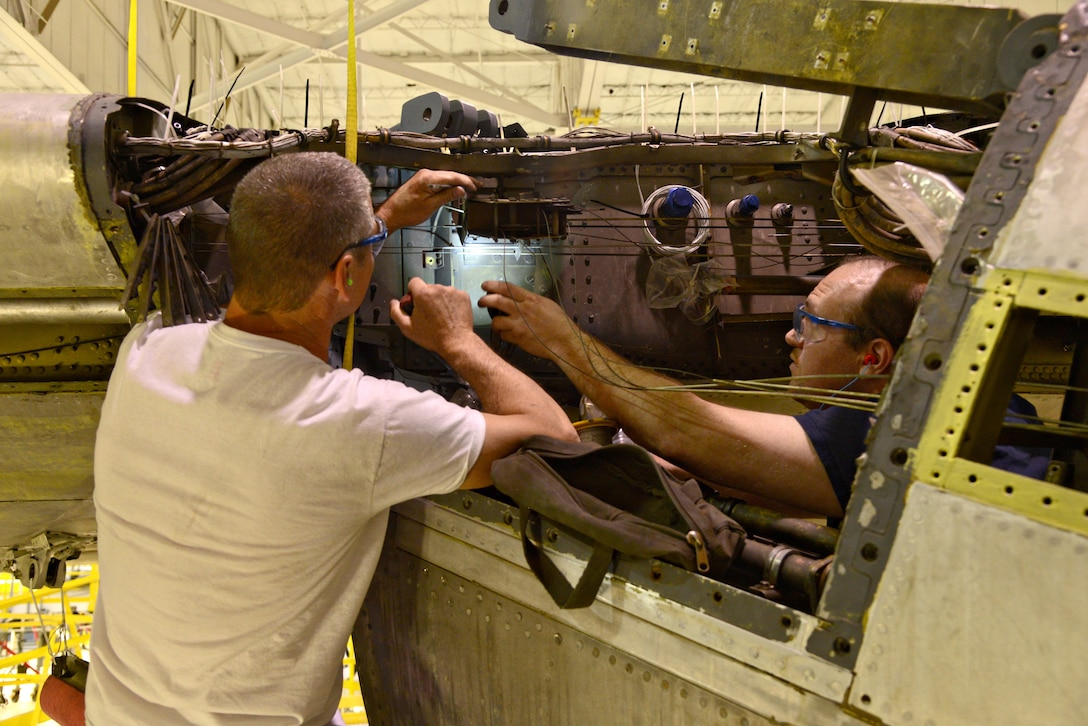 """Chris Carson and Martin Harpster, both aircraft mechanics with the 565th Aircraft Maintenance Squadron, work on throttle cable pullies on the right wing of """"Ghost Rider."""" (Air Force photo by Kelly White/Released)"""