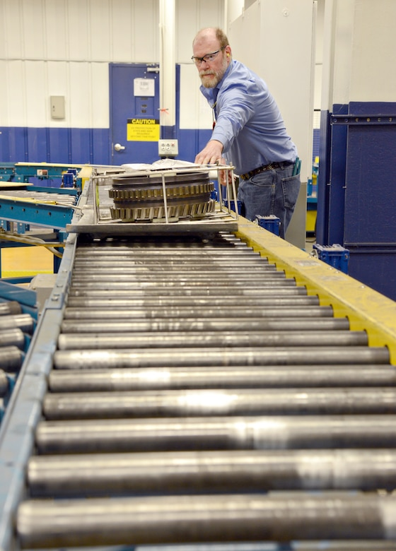 Jason Morrison, the fluorescent penetrant inspection work leader from the 548th Propulsion Maintenance Squadron, places an engine part on a conveyor belt that will be sorted and sent to the correct shop within the Non-Destructive Inspection area. Tinker's NDI shop can perform all five methods of inspection: fluorescent penetrant inspection, magnetic particle inspection, eddy current inspection, ultrasonic inspection and X-ray/radiographic inspection. (Air Force photo by Kelly White/Released)