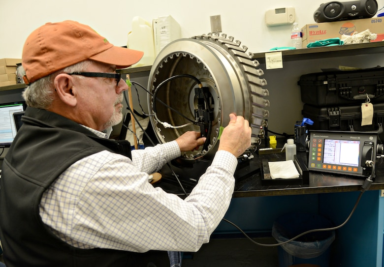 Steve Guinn, the work leader for Eddy Current and Ultrasonic inspections, performs a Phasor Ray inspection on a second stage fan disk for the F110 engine. Ultrasonic sound waves from the ray helps amplify the sound of a compromise, or a crack, in the part. (Air Force photo by Kelly White/Released)