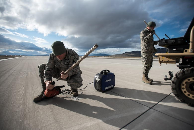 U.S. Air Force Master Sgt. Joshua Selby, ramp coordinator with the Kentucky Air National Guard's 123rd Contingency Response Group, prepares to drill into the runway at Amedee Army Airfield, Calif., to get a core sample to test the strength of the concrete on March 6, 2016. The 123rd CRG is working in conjunction with the U.S. Army's 688th Rapid Port Opening Element and a team from the Defense Logistics Agency to operate Joint Task Force-Port Opening Sangala during a week-long exercise called Operation Lumberjack. The objective of the JTF-PO is to establish an aerial port of debarkation, provide initial distribution capability and set up warehousing for distribution beyond a forward node. (Kentucky Air National Guard photo by Master Sgt. Phil Speck)