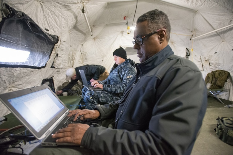 Facial Liban (right), a traffic management specialist for the Defense Logistics Agency's Support Team Black, and Capt. Paul Haslam, Black Team commander, prepare operational reports at Amedee Army Airfield, Calif., on March 7, 2016. The Defense Logistics Agency is working in conjunction with the Kentucky Air National Guard's 123rd Contingency Response Group and the U.S. Army's 688th Rapid Port Opening Element to operate Joint Task Force-Port Opening Sangala during a week-long exercise called Operation Lumberjack. The objective of the JTF-PO is to establish an aerial port of debarkation, provide initial distribution capability and set up warehousing for distribution beyond a forward node. (Kentucky Air National Guard photo by Master Sgt. Phil Speck)