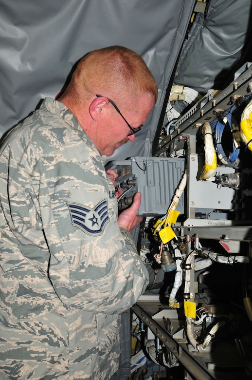U.S. Air Force Staff Sgt. John Milhoan, 161 Air Refueling Wing communications and navigation specialist, changes out an enhanced GPS inertial navigation unit on a KC-135 Stratotanker.  Milhoan was part of a maintenance repair team sent to Wyoming in March to help out fellow Airmen from Eielson Air Force Base, Alaska. (U. S. Air National Guard photo by Master Sgt. Kelly M. Deitloff)