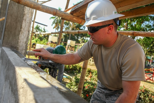 "U.S. Air Force Staff Sgt. Kyle Gould, engineer, assigned to the 673rd Expeditionary Engineer Squadron, flattens a layer of cement to help build a classroom for the Jaena Norte Elementary School, in Capiz, Philippines, during Exercise Balikatan, March 29, 2016. The construction project is one of multiple HCAs taking place during this year's exercise, designed to improve the quality of life for the local populace and strengthen the bond between our two nations. Balikatan, which means ""shoulder to shoulder"" in Filipino, is an annual bilateral training exercise aimed at improving the ability of Philippine and U.S. military forces to work together during planning, contingency and humanitarian assistance and disaster relief operations. (U.S. Marine Corps Combat Camera photo by Cpl. Hilda M. Becerra / Released)"