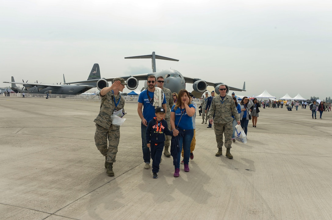 Capt. Ben Worker, U.S. Embassy in Chile, shows groups of children and their caretakers to the F-22 Raptor Static display during the at the 2016 FIDAE Air and Space Trade Show in Santiago, Chile, April 1, 2016. Airmen from around the U.S. came to Chile to participate in the FIDAE Air Show 2016, from March 29– April 3, 2016.  During their stay, they made time to connect one-on-one with members of the community and hosted children from the Make-A-Wish and Teletón Foundations. (U.S. Air Force photo by Tech. Sgt. Heather Redman/Released)