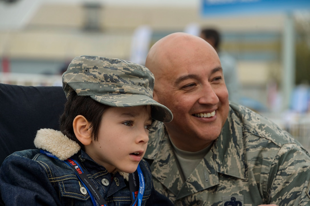 Chief Master Sgt. Jose Barraza, 12th Air Force (Air Forces Southern) command chief, shows a young boy the aircraft on display at the 2016 FIDAE Air and Space Trade Show in Santiago, Chile, April 1, 2016. Airmen from around the U.S. came to Chile to participate in the FIDAE Air Show 2016, from March 29– April 3, 2016.  During their stay, they made time to connect one-on-one with members of the community and hosted children from the Make-A-Wish and Teletón Foundations. (U.S. Air Force photo by Tech. Sgt. Heather Redman/Released)