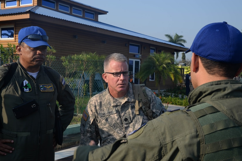 U.S. Army Lt. Col. Daniel Moore talks with Honduran Lt. Col. Julio Hernandez and other members of the Honduran Air Force April 1, 2016, Tela, Honduras, to coordinate aerial-firefighting efforts along the northern coast of Honduras. Honduran President Juan Orlando Hernandez requested the support of U.S. air assets to help the Honduran Fire Department, Air Force and Army, which were already engaged in helping extinguish the forest fire near Tela. (U.S. Air Force photo by Staff Sgt. Westin Warburton/ Released)