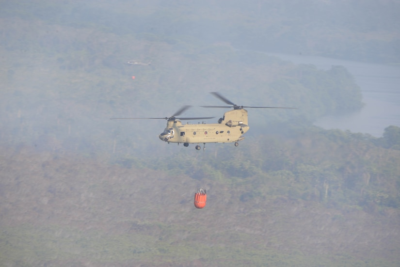 A U.S. Army CH-47 Chinook and UH-60 Black Hawk provide Bambi Bucket firefighting capabilities in support of a Honduran effort to extinguish a forest fire, March 31, 2016, near Tela Honduras, at the request of Honduran President Juan Orlando Hernandez. The two aircraft were a part of a package of helicopters that Joint Task Force-Bravo, located at Soto Cano Air Base, Honduras, sent to help the Hondurans respond to the fire. (U.S. Air Force photo by Staff Sgt. Westin Warburton/ Released)