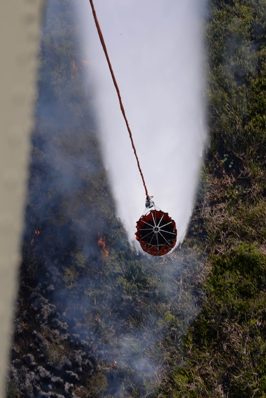 A U.S. Army CH-47 Chinook uses a Bambi Bucket to drop water on a fire March 31, 2016, near Tela, Honduras, at the request of Honduran President Juan Orlando Hernandez. The Chinooks were a part of aircraft from the 1-228th Aviation Regiment to support the Honduran Fire Department, Air Force and Army in the firefighting efforts. (U.S. Air Force photo by Staff Sgt. Westin Warburton/ Released)