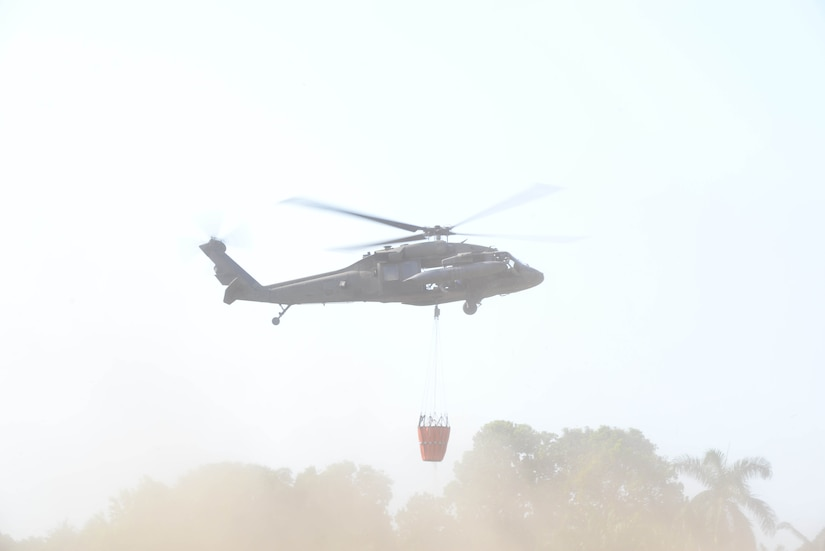 A U.S. Army UH-60 Black Hawk with the 1-228th Aviation Regiment takes off with a Bambi Bucket March 31, 2016, Tela, Honduras, to respond to a request from Honduran President Juan Orlando Hernandez for support in extinguishing a forest fire near Tela. The Honduran Fire Department, Air Force and Army worked with U.S. air assets from Joint Task Force-Bravo at Soto Cano Air Base, Honduras, to control and extinguish the fire. (U.S. Air Force photo by Staff Sgt. Westin Warburton/ Released)
