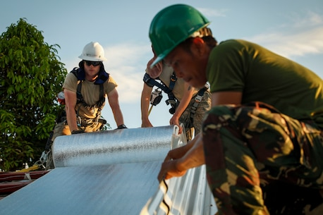 "U.S. Air Force Senior Airman Josiah Sorrels, engineer, assigned to the 673D Expeditionary Engineer Squadron and a Philippine army soldier lay down thermal insulation at Jaena Norte Elementary School in Capiz, Philippines, as part of a humanitarian civic assistance (HCA) project during Exercise Balikatan 2016, April 2, 2016. The construction project is one of multiple HCAs taking place during this year's exercise, designed to improve the quality of life for the local populace and strengthen the bond between our two nations. Balikatan, which means ""shoulder to shoulder"" in Filipino, is an annual bilateral training exercise aimed at improving the ability of Philippine and U.S. military forces to work together during planning, contingency and humanitarian assistance and disaster relief operations."