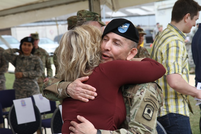 Col. Miguel Castellanos, outgoing commander of the 361st Civil Affairs Brigade, hugs Stacey Novak, wife of the incoming commander Col. John Novak after the 361st change of command ceremony Sunday, April 3, 2016 at Daenner Kaserne in Kaiserslautern, Germany.