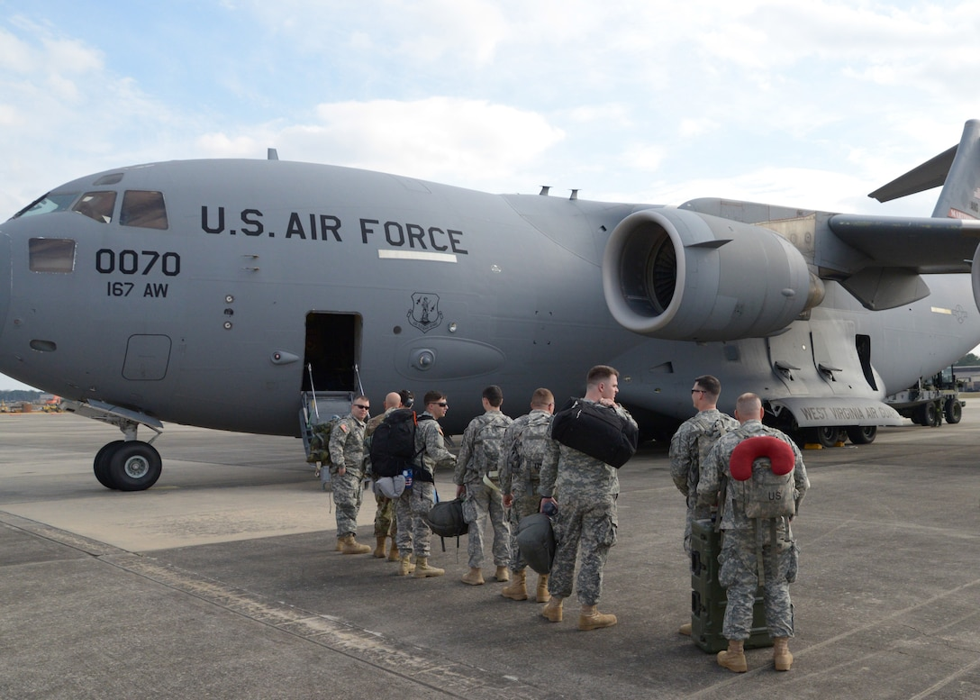 National Guard Soldiers assigned to North Carolina, South Carolina and West Virginia prepare to board a West Virginia Air National Guard C-17 Globemaster III inbound for Moldova at Pope Airfield, N.C., March 5, 2016. The Soldiers will be participating in an overseas deployment training exercise with a Moldovan reconnaissance company, which will prepare them to conduct support missions during a rotation at the National Training Center. (U.S. Army National Guard Photo by Staff Sgt. Brendan Stephens, 382nd Public Affairs Detachment/Released)