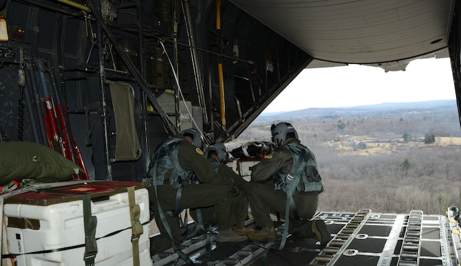 Loadmasters assigned to the 103rd Airlift Wing prepare to drop a bundle out the back of a C-130 Hercules over the 439th Westover Air Reserve Base, Chicopee, Mass. The Flying Yankees, in coordination with the 439th, are conducting a Low Cost Low Altitude air drop. LCLA airdrops enable the C-130 to efficiently drop supplies or any crucial materials required by those on the battlefield at a below average altitude to lessen the threat to whomever may be receiving the care package. (U.S. Air National Guard photo by Senior Airman Emmanuel Santiago)