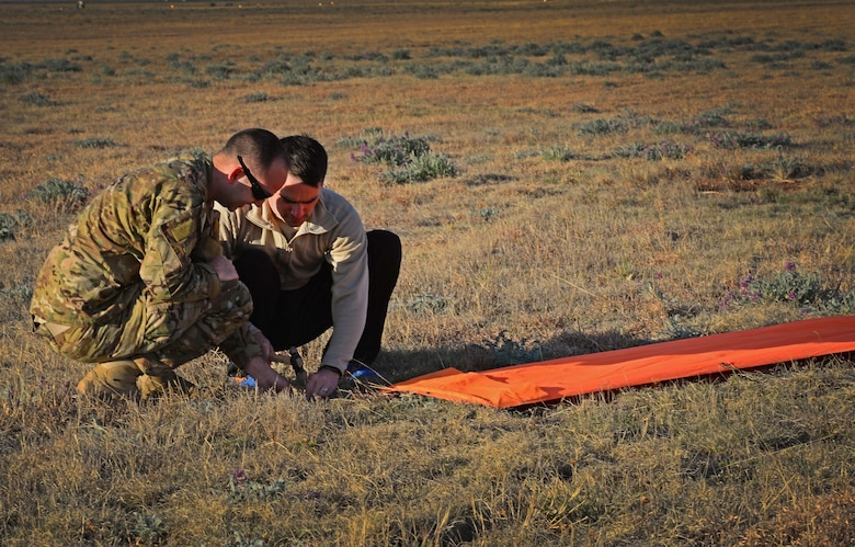 Two team members with the 26th Special Tactics Squadron prepare secure a marker for a landing zone March 25, 2016, at Cannon Air Force Base, N.M. This helped other 26th STS members performing routine practice jumps over the Cannon flightline safely identify their target landing area. (U.S. Air Force photo/Staff Sgt. Alexx Pons)