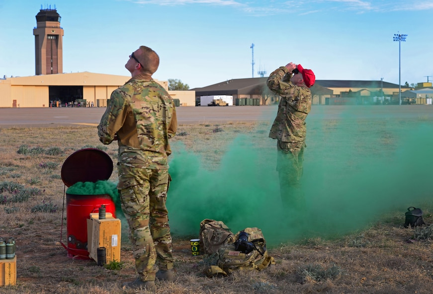 Members of the 26th Special Tactics Squadron watch as teammates parachute down from an aircraft overhead March 25, 2016, at Cannon Air Force Base, N.M. Dozens of 26th STS members performed routine practice jumps over the Cannon flightline, and relied on ground crews to use signals to help them safely touch-down at the designated landing zone. (U.S. Air Force photo/Staff Sgt. Alexx Pons)
