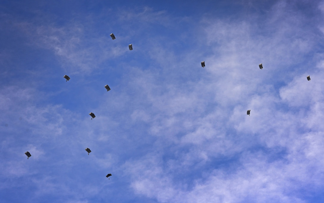 A dozen members of the 26th Special Tactics Squadron parachute down from an aircraft over the flightline March 25, 2016, at Cannon Air Force Base, N.M. Special Tactics Airmen train to maintain operational readiness, able to infiltrate into areas where aircraft cannot land. (U.S. Air Force photo/Staff Sgt. Alexx Pons)