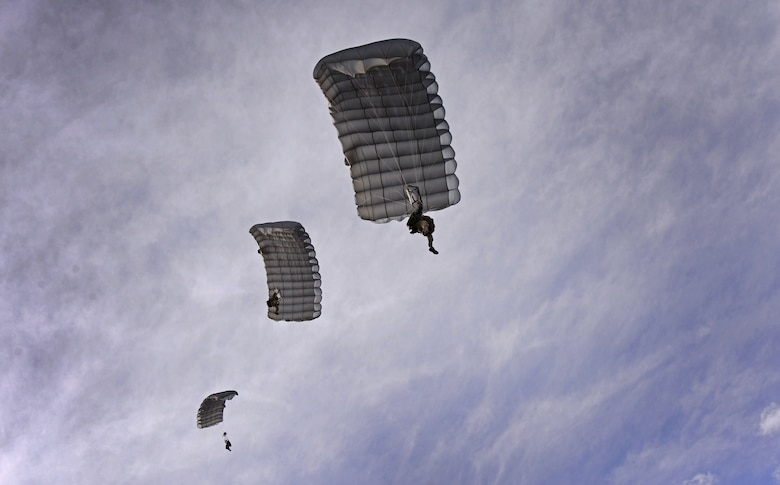 Three members of the 26th Special Tactics Squadron parachute down over the flightline March 25, 2016, at Cannon Air Force Base, N.M. Air Commandos with the 26th STS performed routine practice jumps as part of maintaining operational readiness. (U.S. Air Force photo/Staff Sgt. Alexx Pons)