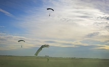 Several 26th Special Tactics Squadron members approach their final touch-down onto a landing zone March 25, 2016, at Cannon Air Force Base, N.M. Air Commandos with the 26th STS performed routine practice jumps as part of maintaining operational readiness. (U.S. Air Force photo/Staff Sgt. Alexx Pons)
