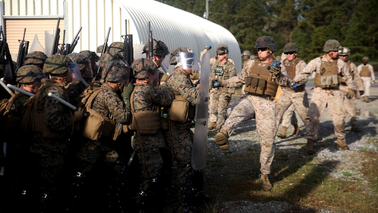 A riot control squad, comprised of Marines with Combat Logistics Battalion 2, battles a notional opposing force during the unit's non-lethal weapons training final exercise at Marine Corps Base Camp Lejeune, North Carolina, March 25, 2016. The battalion had to qualify through the Expeditionary Operations Training Group, in preparation for their upcoming deployment with Special Purpose Marine Air-Ground Task Force-Crisis Response-Africa.