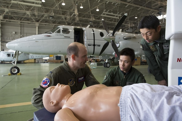 (Left to right) U.S. Air Force 1st Lt. Anthony Pergola, 459th Airlift Squadron C-12 pilot, talks about an Aeromedical Evacuation Spectrum Bed to Japan Air Self-Defense Capt. Daiki Ishihara, 402nd Squadron C-1 pilot, and JASDF Tech. Sgt. Shoji Nagata, 402nd Squadron C-1, U-4 loadmaster, at Yokota Air Base, Japan, March 30, 2016. Members with the 459th AS demonstrated Aeromedical Evacuation procedures of a C-12 Huron to JASDF members to improve the working relationship between JASDF and USAF. (U.S. Air Force photo by Yasuo Osakabe/Released)
