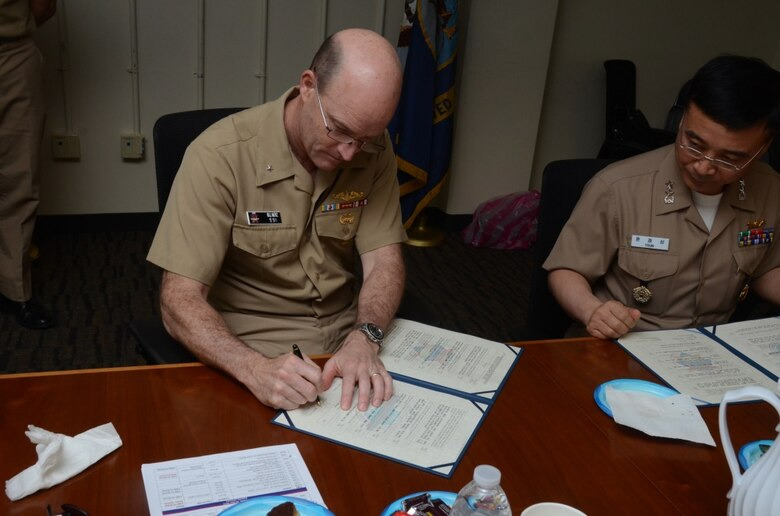 160331-N-YM720-263 SANTA RITA, Guam (March 31, 2016) Rear Adm. William Merz, commander, Submarine Group 7, left, and Rear Adm. Youn Jeong Sang, commander, Submarine Force, Republic of Korea Navy (ROKN), sign a formal agreement at the conclusion of the 43rd Submarine Warfare Committee Meeting (SWCM) reaffirming the longstanding relationship between the two countries and pledging continued support between the two submarine forces. SWCM is a bilateral discussion between the U.S. and ROKN submarine forces designed to foster the partnership and focuses on submarine tactics, force integraton and future submarine development. (U.S. Navy photo by MC3 Allen McNair/Released)