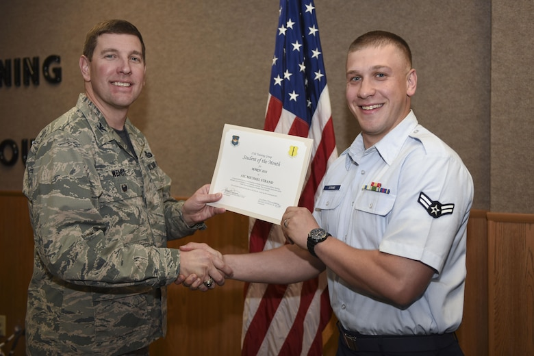 U.S. Air Force Col. Kurt A. Wendt, 17th Training Group Deputy Commander, presents the 315th Training Squadron Enlisted Student of the Month award for March 2016 to Airman 1st Class Michael Strand at the Brandenburg Hall on Goodfellow Air Force Base, Texas, April 1, 2016. (U.S. Air Force photo by Airman Chase Sousa/Released)