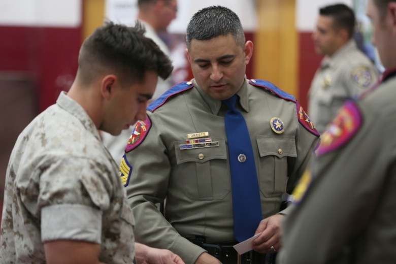Sergeant Octavio Ureste, recruiter, Texas Department of Public Safety, talks to Cpl. Will Parker, refrigeration and air conditioning mechanic, Marine Wing Support Squadron 374, about his agency during the Education and Career Fair at the West Gym, March 23, 2016.( Official Marine Corps photo by Cpl. Julio McGraw/Released)